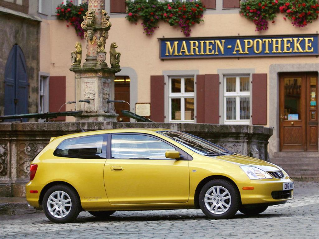 Żółta Honda Civic VII zdjęcie z boku na tle włoskiej apteki w mieście