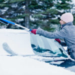 Kobieta usuwa śnieg z auta