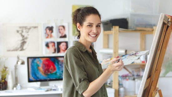 Stylish young Caucasian woman with dark hair taking part in class and workshop for artists, feeling happy and excited, standing in studio in front of easel and smiling. Art, learning and education