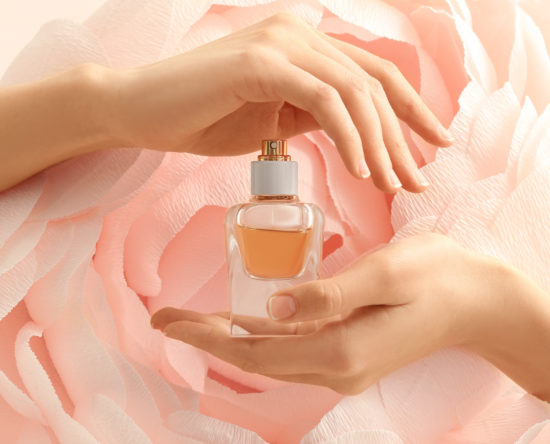 Hands of beautiful young woman with bottle of floral perfume against decorative artificial flower