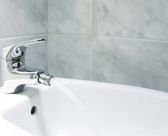 Detail of the faucet of a bidet with running water