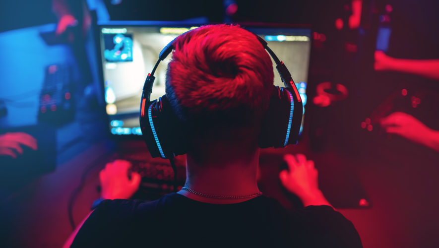 Professional gamer playing online games tournaments pc computer with headphones, Blurred red and blue background
