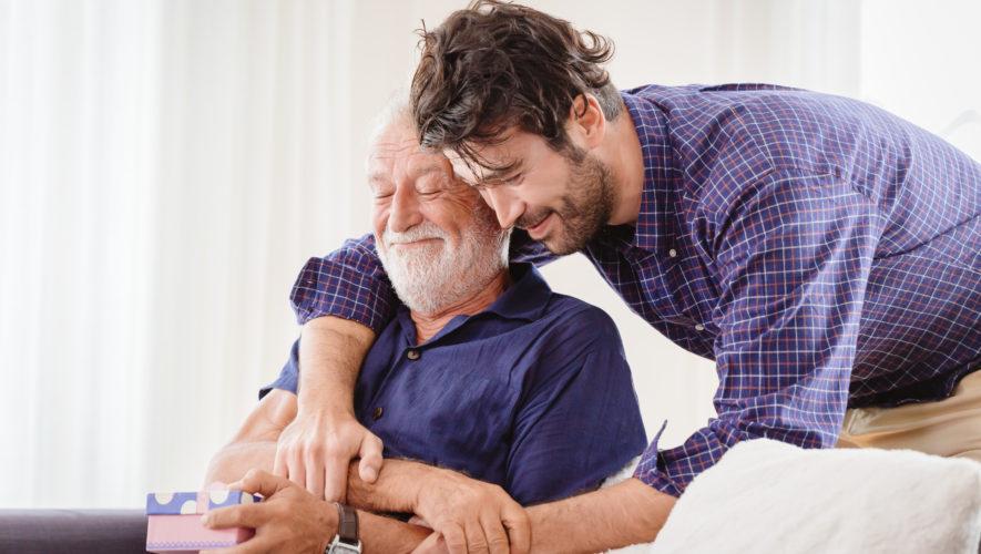 młody mężczyzna obejmuje ojca wręczając mu jednocześnie pudełko z prezentem