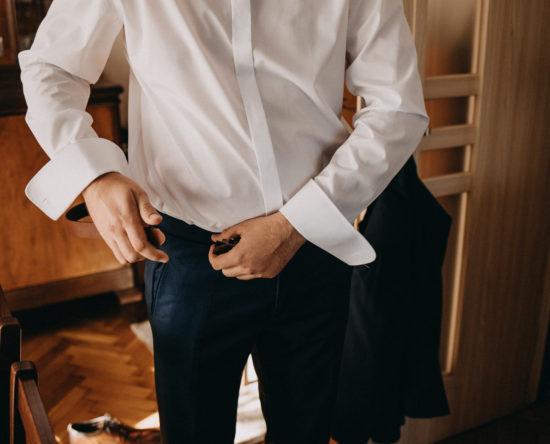 Pan młody zakłada skórzany pasek lub dominacja mężczyzny w garniturze