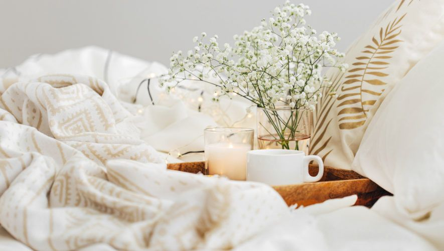 Wooden tray of coffee and candles with flowers on bed