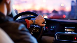 Driving a car at night - young man driving her car