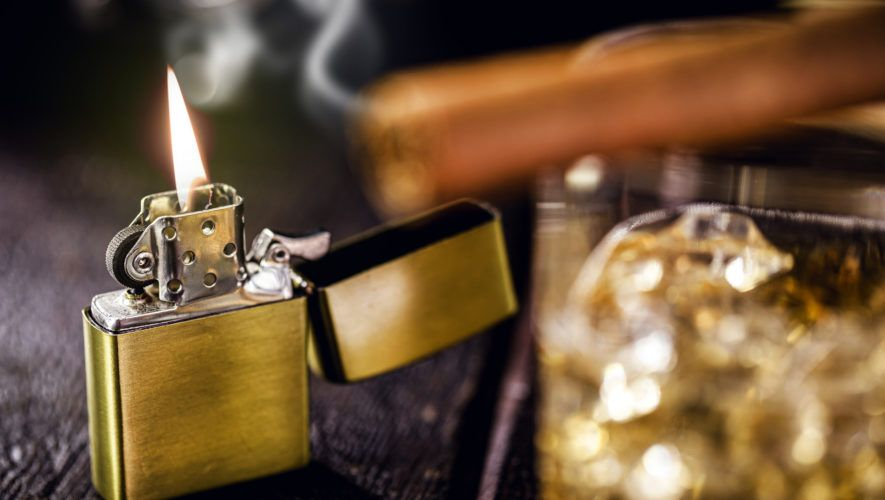 vintage windproof lighter on rustic wooden background. Access cigar and glass of alcohol in front, spot focus